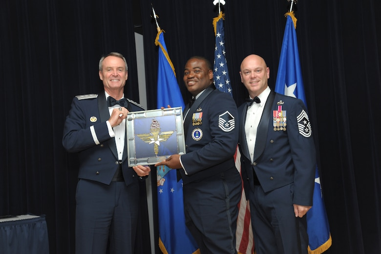 Master Sgt. Eric Hart, 344th Recruiting Squadron, Waco, Texas, receives an award from Lt. Gen. Darryl Roberson, commander, Air Education and Training Command and AETC Command Chief Master Sgt. David Staton during a ceremony here, June 16. Hart was selected as the AETC Recruiter of the Year. (U.S. Air Force photo by Joel Martinez)
