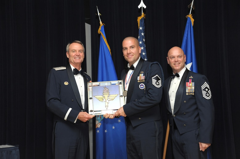 Tech. Sgt. Kyle Mullen, Technical Training Operations Center, Keesler Air Force Base, Mississippi, receives an award from Lt. Gen. Darryl Roberson, commander, Air Education and Training Command and AETC Command Chief Master Sgt. David Staton during a ceremony here, June 16. Mullen was selected as the AETC Military Training Leader of the Year. (U.S. Air Force photo by Joel Martinez)