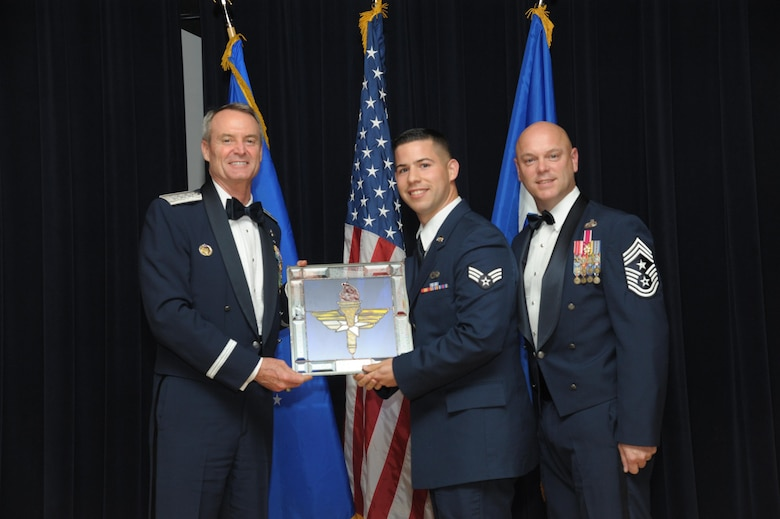 Senior Airman Jan Diaz Garcia, 56th Maintenance Group, Luke Air Force Base, Arizona, receives an award from Lt. Gen. Darryl Roberson, commander, Air Education and Training Command and AETC Command Chief Master Sgt. David Staton during a ceremony here, June 16. Diaz Garcia was selected as the AETC Honor Guard Member of the Year. (U.S. Air Force photo by Joel Martinez)
