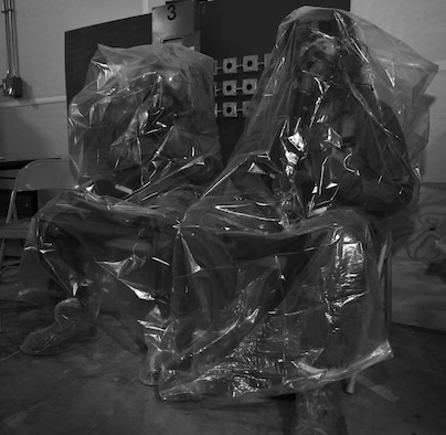 Aircrew members sit in plastic bags before processing a simulated decontamination line at Hurlburt Field, Fla., June 9, 2016. Air Force Special Operations Command's operations directorate ran a realistic, scenario-based, training program for 16 aircrew flight equipment (AFE) Airmen from eight southern United States bases. (U.S. Air Force photo / Staff Sgt. Melanie Holochwost)