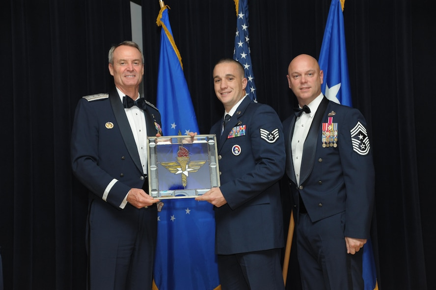Staff Sgt. Richard Bates, 47th Flying Training Wing, Laughlin Air Force Base, Texas, receives an award from Lt. Gen. Darryl Roberson, commander, Air Education and Training Command and AETC Command Chief Master Sgt. David Staton during a ceremony here, June 16. Bates was selected as the AETC Honor Guard Program Manager of the Year. (U.S. Air Force photo by Joel Martinez)
