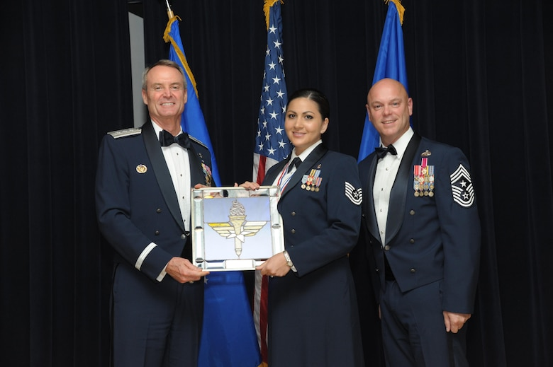 Tech. Sgt. Cassandra Cruz, 81st Force Support Squadron, Keesler Air Force Base, Mississippi, receives an award from Lt. Gen. Darryl Roberson, commander, Air Education and Training Command and AETC Command Chief Master Sgt. David Staton during a ceremony here, June 16. Cruz was selected as the AETC NCO of the Year. (U.S. Air Force photo by Joel Martinez)