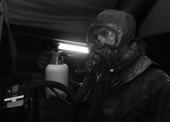 """An aircrew flight equipment specialist sprays a simulated bleach solution on an aircrew member during the """"final exam"""" phase of an Air Staff exerise rehearsing deployed decontamination processes. Air Force Special Operations Command's operations directorate ran a realistic, scenario-based, training program for 16 Airmen from eight southern United States bases. (U.S. Air Force photo / Staff Sgt. Melanie Holochwost)"""