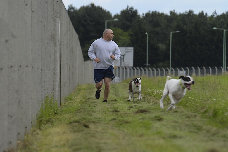 U.S. Air Force Master Sgt. Matthew Deel, 100th Civil Engineer Squadron facility superintendent, runs with his dogs in the new dog park June 16, 2016, on RAF Mildenhall, England. The park enables Airmen and their families to exercise and play with their dogs in a safe environment on base. (U.S. Air Force photo by Staff Sgt. Micaiah Anthony/Released)