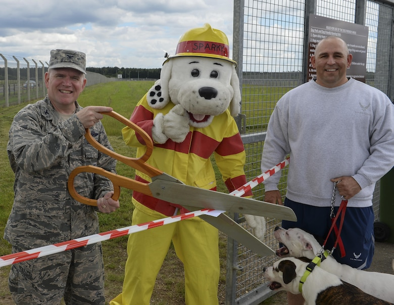 U.S. Air Force Col. Thomas Torkelson, left, 100th Air Refueling Wing commander, cuts the ribbon for the new dog park with Sparky the Fire Dog and Master Sgt. Matthew Deel, 100th Civil Engineer Squadron facility superintendent, June 16, 2016,on RAF Mildenhall, England. The park is open to all members with base access from sunrise to sunset. (U.S. Air Force photo by Staff Sgt. Micaiah Anthony/Released)