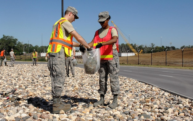 U.S. Air Force 1st Lieutenant Michael Day, 55th Operational Support Squadron, left, and U.S. Air Force 2nd Lt. Valyn Gipson, 55th Medical Support Squadron, pull weeds from the rock beds near Offutt's STRATCOM gate June 15 while volunteering as part of the Installation Pride Initiative. (U.S. Air Force photo by Delanie Stafford/Released)