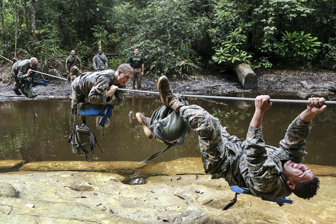 U.S. soldiers maneuver across a wire cable over a river during a team obstacle course event at the French jungle warfare school in Gabon, France, June 10, 2016. Army photo by Spc. Yvette Zabala-Garriga