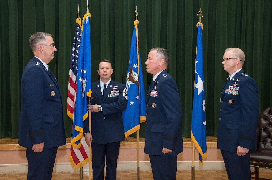 """General John Hyten, Commander, Air Force Space Command, prepares to transfer the 24AF guidon from Maj. Gen. Burke """"Ed"""" Wilson to Maj. Gen. Christopher Weggeman during the 24th Air Force change of command ceremony 17 June. Command Chief Master Sgt. Brendan Criswell (center) served as guidon bearer during the ceremony.  (US Photo by Johnny Saldivar)"""