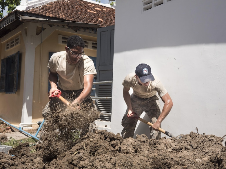 U.S. Air Force Senior Airman Michael Bailey, 124th Civil Engineer Squadron, Idaho Air National Guard, and Airman 1st Class Joseph Walters, Joint Base Pearl Harbor-Hickam's 647th Civil Engineer Squadron water and fuels maintainer shovel dirt for a drainage pipe at a health center during Pacific Angel 16-2 June 15, 2016, in Kampot Province, Cambodia. Pacific Angel helps cultivate common bonds and foster goodwill between the U.S., Cambodia, and other participating nations as they conduct multilateral humanitarian assistance and civil military operations together. The five nations participating in Pacific Angel 16-2 Cambodia include the U.S., Australia, Cambodia, Vietnam and Thailand. (U.S. Air Force photo by Senior Airman Omari Bernard/Released)