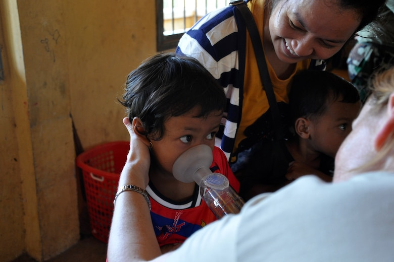 U.S. Air Force Capt. Tasha Hellu, a pediatric physician deployed from the 36th Medical Group, Anderson Air Force Base, Guam, teaches a young Cambodian girl to breath in medicine to treat asthma June 13, 2016, during Pacific Angel 16-2 in Kampot Province, Cambodia. The health services outreach team set up a mobile clinic at two different sites throughout the week, Por Thivong Primary School in Tuek Chhou district June 13-15, and at the Ang Chum Trapaing Chhuk Secondary School in Kampong Trach district June 16-18. The clinics included general health, optometry, dental, family medicine and physical therapy services, as well as a small pharmacy. (U.S. Air Force photo by Capt. Susan Harrington/Released)