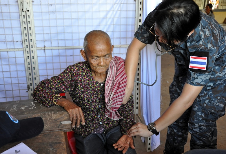 Royal Thai Air Force Flight Lt. Chatchawal Chantaphet, a family practice physician, listens to the heart of an elder Cambodian woman June 13, 2016, during Pacific Angel 16-2 in Kampot Province, Cambodia. With the help of interpreters, multinational doctors and medical technicians provided acute care and educated patients on preventative health measures and self-treatments for various ailments. Engagements such as Pacific Angel help cultivate partner relationships and improve our integrated operations throughout the Indo-Asia-Pacific region. (U.S. Air Force photo by Capt. Susan Harrington/Released)