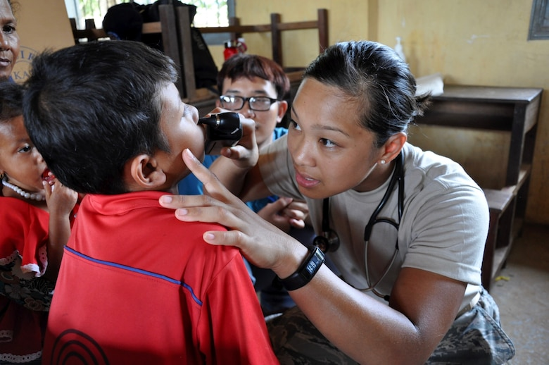 U.S. Air Force Staff Sgt. Sheena Raya Amaya examines a young Cambodian boy June 14, 2016, during Pacific Angel 16-2, a humanitarian assistance/civil-military operation in Kampot Province, Cambodia. Skilled medics from both military and non-governmental agencies around the globe came to provide hospital quality care to patients during the humanitarian assistance/civil military operation mission. Pacific Angel ensures that the region's militaries are prepared to work together to address humanitarian crises in case of natural disasters. (U.S. Air Force photo by Capt. Susan Harrington/Released)
