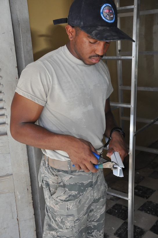 Airman First Class Demarcus Smith, an electrical systems apprentice with the 647th Civil Engineer Squadron, Joint Base Pearl Harbor-Hickam, Hawaii, uses clippers to shorten a panel, June 16, 2016, as part of Pacific Angel 16-2 in Kampot Province, Cambodia. Smith, along with a team of U.S., Cambodian and Australian engineers worked to repair four local schools and two provincial health clinics during the humanitarian mission designed to promote interoperability between partner nations. (U.S. Air Force photo by Capt. Susan Harrington/Released)