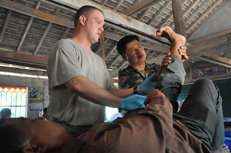 U.S. Air Force Tech. Sgt. Michael Lewis and Royal Cambodian Armed Forces Capt. Tob Vuthy treat a patient for lower back pain June 17, 2016, during Pacific Angel 16-2 in Kampot Province, Cambodia. Throughout the course of the week doctors, dentists, and pharmacists from the U.S., Cambodia, Australia, Vietnam and Thai militaries and two non-governmental organizations, along with 65 volunteers from the provincial hospital and local villages, saw more than 3,400 patients at two different sites. Together they provided general health, dental, optometry, pediatrics, and physical therapy services. (U.S. Air Force photo by Capt. Susan Harrington/Released)