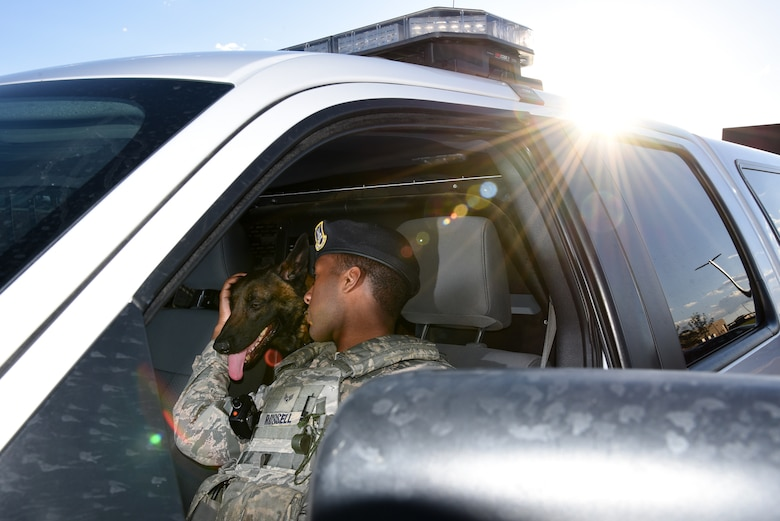 Senior Airman Tariq Russell, 21st Security Forces Squadron military working dog handler, praises his dog, Ppaul, before heading to his next job at Peterson Air Force Base, Colo., June 14, 2016. The relationship between Russell and Ppaul was commended by leadership as being one of the strongest they have witnessed. (U.S. Air Force photo by Airman 1st Class Dennis Hoffman)