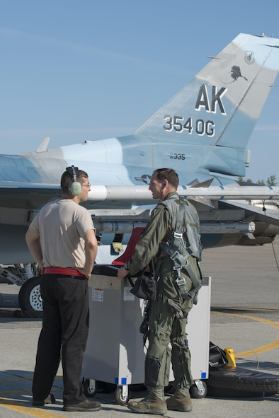 U.S. Air Force Staff Sgt. Dale LeCrone, a 354th Aircraft Maintenance Squadron dedicated crew chief, talks with Col. Brian Toth, the 354th Operations Group commander, before performing pre-flight checks June 16, 2016, during RED FLAG-Alaska (RF-A) 16-2, at Eielson Air Force Base, Alaska. As a prior 353rd Combat Training Squadron commander, Toth has held multiple roles in RF-A and uses that knowledge to make the joint training exercise as successful as possible. (U.S. Air Force photo by Staff Sgt. Ashley Nicole Taylor/Released)
