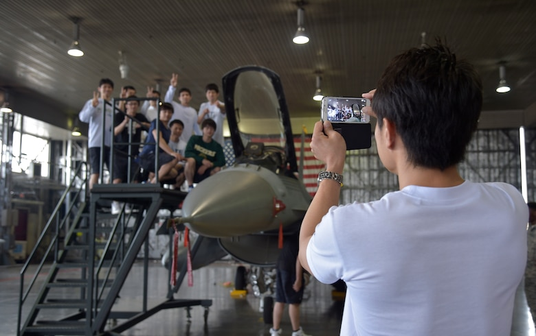 Members of the Japan Railway East Akita Peckers basketball team tour a static display of an F-16 Fighting Falcon at Misawa Air Base, Japan, June 17, 2016. The team was briefed on the 35th Fighter Wing mission and viewed F-16s before taking part in a basketball camp and game. (U.S. Air Force photo by Senior Airman Deana Heitzman)