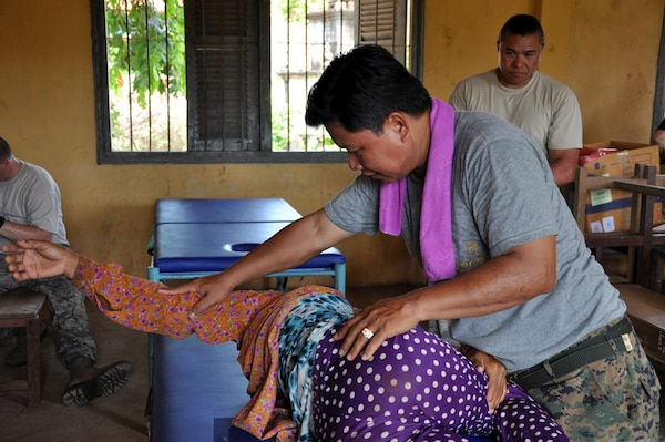 Royal Cambodian Air Force Capt. Tob Vuthy treats a patient for lower back pain June 14, 2016, during Pacific Angel 16-2 in Kampot Province, Cambodia. Multinational doctors, dentists and pharmacists treated patients in the province as part of the humanitarian assistance mission designed to enhance participating nations' humanitarian assistance and disaster relief capabilities while providing needed services to people throughout the Indo-Asia-Pacific. Pacific Angel 16-2 included general health, dental, optometry, pediatrics, physical therapy and engineering programs as well a various subject-matter expert exchanges. (U.S. Air Force photo by Capt. Susan Harrington/Released)