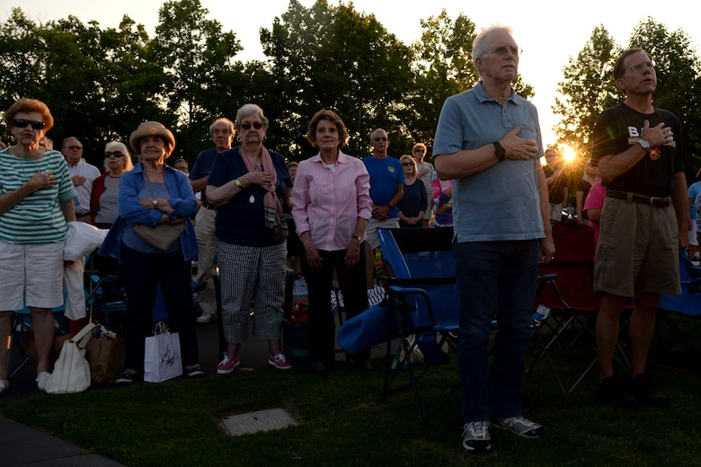 Audience members stand while the U.S. Air Force Band performs the National Anthem at the Air Force Memorial in Arlington, Va., June 17, 2016. During the performance, the Macy's Band Selection Committee announced the United States Air Force Band and Honor Guard will represent the Air Force and perform in New York City in the 2017 Macy's Thanksgiving Day Parade. (U.S. Air Force photo/Tech. Sgt. Matt Davis)
