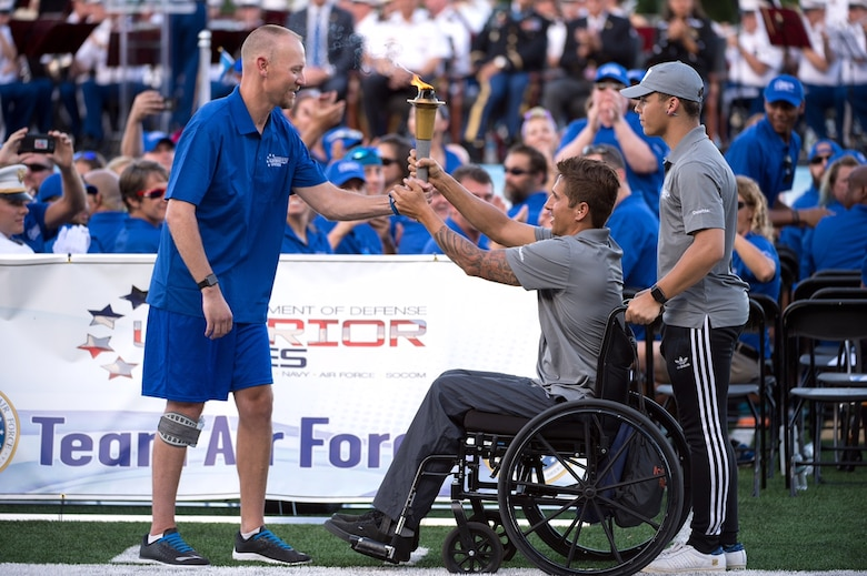 Retired Air Force Capt. Chris Cochrane, left, accepts the 2016 Department of Defense Warrior Games torch from Navy Lt. Ramesh Haytasingh of the U.S. Special Operations Command team during opening ceremonies at the U.S. Military Academy in West Point, N.Y., June 15, 2016. With Haytasingh is his son, Tobias. (Department of Defense photo/EJ Hersom)