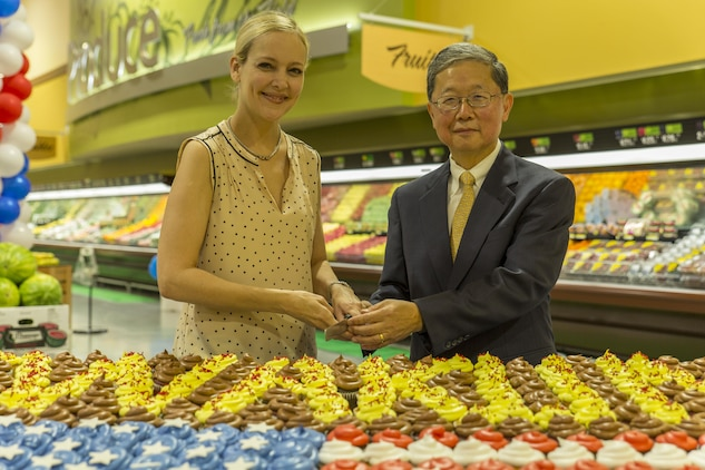 Kim Shipley, a station resident, left, and Joseph H. Jeu, director and CEO of the Defense Commissary Agency, cut the cake during the grand opening ceremony at Marine Corps Air Station Iwakuni, Japan, June 21, 2016. Designed to anticipate and meet the needs of shoppers, the new grocery store is approximately 50 percent larger, with 52,710 total square feet and is located between the Kintai Inn and Kawashimo housing area.  Sections of the improved facility include fresh produce, meat and frozen departments, an international delicatessen, a bakery and fresh, handmade sushi. (U.S. Marine Corps photo by Lance Cpl. Aaron Henson/Released)