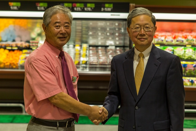 Buddie Kolath, store director, left, and Joseph H. Jeu, director and CEO of the Defense Commissary Agency, shake hands during the grand opening ceremony for the new commissary on Marine Corps Air Station Iwakuni, Japan, June 21, 2016. Designed to anticipate and meet the needs of shoppers, the new grocery store is approximately 50 percent larger, with 52,710 total square feet and is located between the Kintai Inn and Kawashimo housing area.  The new store features three additional checkout stands, a 22,000 square foot sales floor and an assortment of approximately 10,000 items. (U.S. Marine Corps photo by Lance Cpl. Aaron Henson/Released)