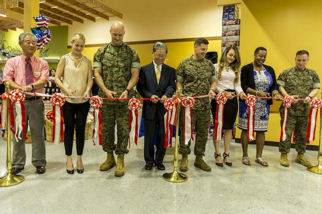 From left to right, Buddie Kolath, store director, Kim Shipley, a station resident, U.S. Marine Corps Col. Daniel Shipley, Marine Aircraft Group 12 commanding officer, Joseph H. Jeu, director and CEO of the Defense Commissary Agency, U.S. Marine Corps Col. Robert V. Boucher, station commanding officer, Marcela Londono and Carla Bates, station residents, and U.S. Marine Corps Sgt. Maj. Christopher Garza, station sergeant major, conduct the ribbon-cutting ceremony during the grand opening of the new commissary at Marine Corps Air Station Iwakuni, Japan, June 21, 2016. Designed to anticipate and meet the needs of shoppers, the new grocery store is approximately 50 percent larger, with 52,710 total square feet and is located between the Kintai Inn and Kawashimo housing area. (U.S. Marine Corps photo by Lance Cpl. Aaron Henson/Released)