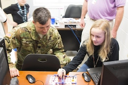 Lt. Col. Nathan Molica, deputy commander, participated in the Charleston Metro Chamber of Commerce's Principal for a Day program where he shadowed the principal of Cario Middle School to learn about their STEM program. Here, he learns about nigh light circuitry from one of their students.