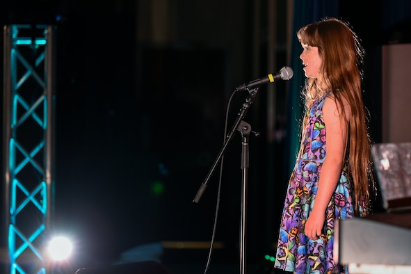 """PETERSON AIR FORCE BASE, Colo. – Alexis Remy sings the """"Fight Song"""" by Rachel Platten during the Peterson's Got Talent competition at The Club on Peterson Air Force Base, Colo., June 14, 2016. Remy won first place for the preteen (ages 9-12) category and was presented a trophy and certificate by Col. Doug Schiess, 21st Space Wing commander and Chief Master Sgt. Idalia Peele, 21st Space Wing command chief master sergeant. (U.S. Air Force Photo by Craig Denton)"""