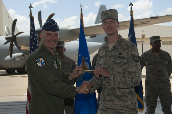 U.S. Air Force Gen. Carlton D. Everhart II, Air Mobility Command commander, presents a ceremonial C-130J key to U.S. Air Force Tech. Sgt. James Kowalski, 19th Aircraft Maintenance Squadron C-130J crew chief, June 20, 2016, at Little Rock Air Force Base, Ark. The final C-130J completed the H-model to J-model transition for the 19th Airlift Wing's fleet. (U.S. Air Force photo/Senior Airman Harry Brexel)