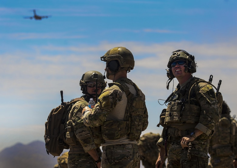 Multiple Joint Terminal Attack Controllers and Combat Controllers watch C-130s fly in formation during the Joint Forcible Entry Exercise portion of the United States Air Force Weapons School Advanced Integration, June 16, 2016. Joint service exercises like the JFEX are integral to maintaining operational cohesiveness between the Air Force and the Army. (U.S. Air Force photo by Airman 1st Class Kevin Tanenbaum)