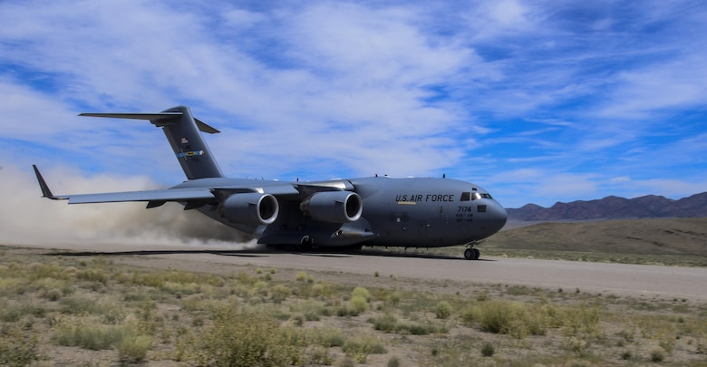 A C-17 Globemaster III, assigned to the 17th Weapons Squadron, Nellis Air Force Base, Nevada, lands on an airstrip in the Nevada Test and Training Range during Joint Forcible Entry Exercise, June 16, 2016. JFEX is a U.S. Air Force Weapons School large-scale air mobility exercise in which participants plan and execute a complex air-land operation in a simulated contested battlefield. (U.S. Air Force photo by Airman 1st Class Kevin Tanenbaum)