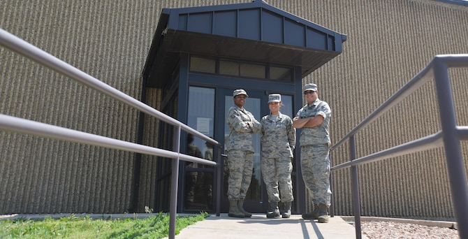 Tech. Sgt. Katrena Holmes, Senior Airman Alyssa Flores and Senior Airman James Boone, 21st Medical Squadron bioenvironmental engineers, stand outside their office's entrance at Schriever Air Force Base, Colorado, Friday, June 17, 2016. The mission of the office is to protect and prevent Airmen from hazardous workplace environments. (U.S. Air Force photo/ Airman William Tracy)