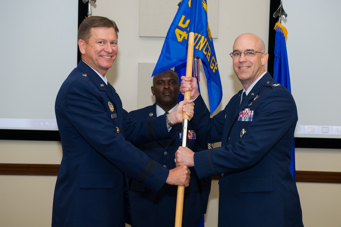 Brig. Gen. Wayne Monteith, 45th Space Wing commander, presents Col. Steven Lang, 45th Launch Group commander, with the guidon during a change of command ceremony June 21, 2016, at Patrick Air Force Base, Fla. Changes of command are a military tradition representing the transfer of responsibilities from the presiding officials to the upcoming official. (U.S. Air Force photo/Benjamin Thacker/Released)