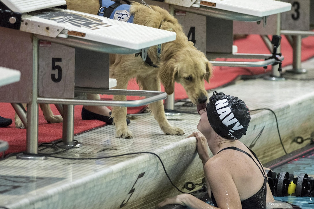 Navy Petty Officer 3rd Class Abbie Johnson gets a kiss from Kona, her military service dog, after competing in a swimming during the 2016 Department of Defense Warrior Games at the U.S. Military Academy in West Point, N.Y., June 20, 2016. DoD photo by Roger Wollenberg