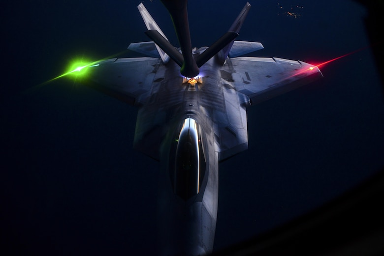 A KC-135, assigned to the 509th Weapons Squadron, Fairchild Air Force Base, Wash., preforms aerial refueling on an F-22 Raptor, assigned to the 433rd Weapons Squadron, Nellis Air Force Base, Nev., over the Nevada Test and Training Range during the United States Air Force Weapons School's Deliberate Strike Night, June 16, 2016. DSN is part of the final seven day Advanced Integration portion of the Weapons School curriculum; testing stealth and conventional airframes abilities to conduct attacks during the hours after the sun sets. (U.S. Air Force photo by Airman 1st Class Kevin Tanenbaum)