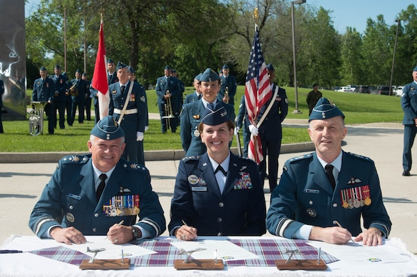 Incoming 1 Canadian Air Division commander MGen. Christian Drouin (left), NORAD and USNORTHCOM commander, Gen. Lori Robinson (center), and outgoing 1 CAD commander MGen. David Wheeler (right), sign the Change of Command scrolls during the 1 CAD Change of Command ceremony at Winnipeg, Manitoba, Canada, June 21, 2016.