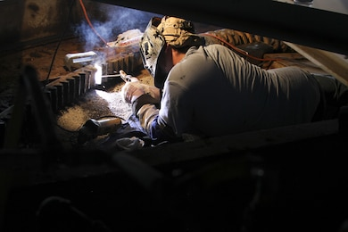 Christopher West, a welder with Norfolk Machine and Welding Inc., contracted by the Norfolk District, U.S. Army Corps of Engineers, works on repairing damaged gear teeth on the North Landing Bridge here, June 21, 2016. The repairs were needed to fix damage caused by a barge striking the bridge on June 4. (U.S. Army photo/Patrick Bloodgood)