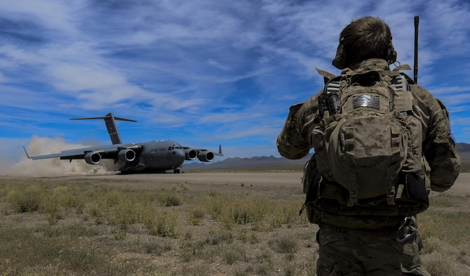 A Combat Controller watches as a C-17 assigned to the 17th Weapons Squadron, Nellis Air Force Base, Nevada, lands on an airstrip in the Nevada Test and Training Range during Joint Forcible Entry Exercise, June 16, 2016. The exercise demonstrates the Air Force's ability to tactically deliver and recover combat forces via air drops and combat landings in a contested environment. (U.S. Air Force photo by Airman 1st Class Kevin Tanenbaum)