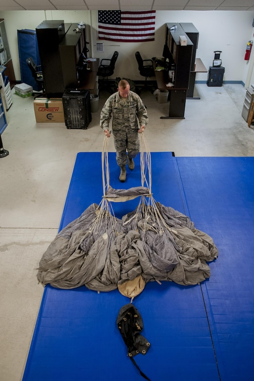 U.S. Air Force Tech. Sgt. Matthew Michels, 31st Rescue Squadron aircrew flight equipment assistant NCO in charge, straightens parachute chords while parachute packing June 20, 2016, at Kadena Air Base, Japan. Michels ensures 31st RQS pararescuemen can don safe parachute packs that have passed intensive safety checks. (U.S. Air Force photo by Senior Airman Peter Reft)