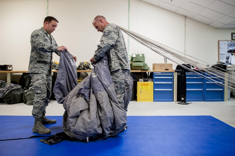 U.S. Air Force Senior Airman Erik Merrill, 31st Rescue Squadron aircrew flight equipment journeyman, and Tech. Sgt. Matthew Michels, 31st RQS aircrew flight equipment assistant NCO in charge, fold a parachute canopy June 20, 2016, at Kadena Air Base, Japan. Merrill and Michels ensure the safety of aircrews jumping from aircraft by assembling and maintaining parachute packs according to strict guidelines and procedures. (U.S. Air Force photo by Senior Airman Peter Reft)