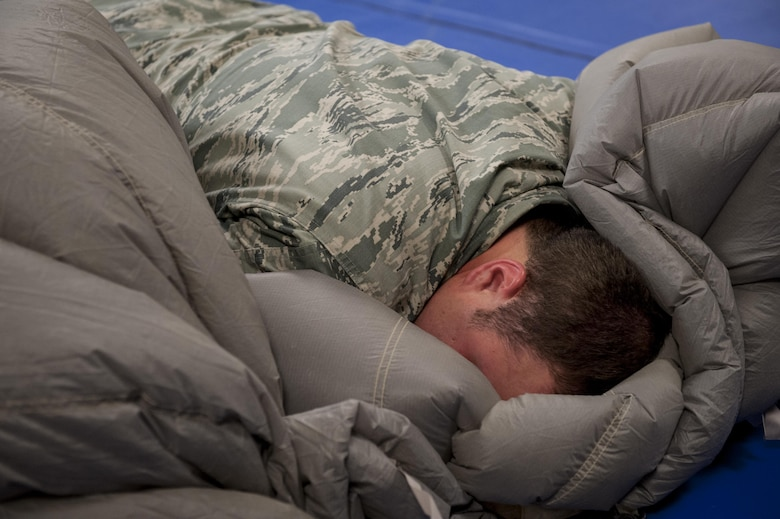 U.S. Air Force Senior Airman Erik Merrill, 31st Rescue Squadron aircrew flight equipment journeyman, cocoons a parachute canopy June 20, 2016, at Kadena Air Base, Japan. Merrill applied his entire body weight on top of the canopy in order to push out all the air between folds, enabling him to pack it into a small deployment bag. (U.S. Air Force photo by Senior Airman Peter Reft)