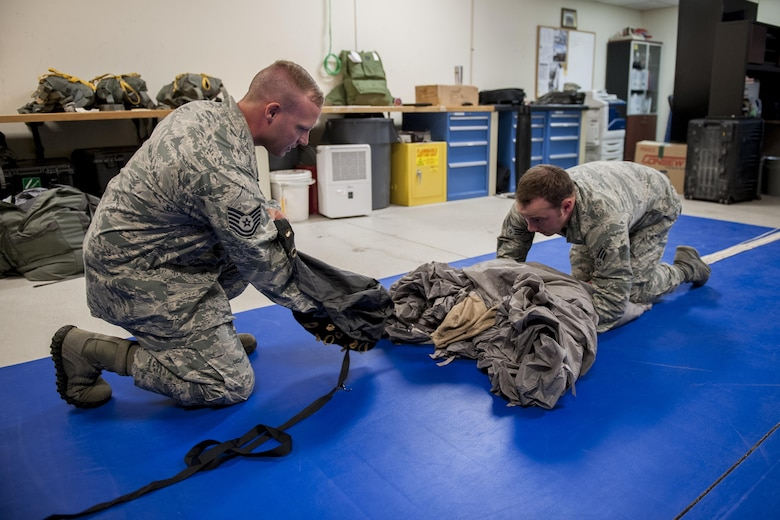 U.S. Air Force Tech. Sgt. Matthew Michels, 31st Rescue Squadron aircrew flight equipment assistant NCO in charge, and Senior Airman Erik Merrill, 31st RQS aircrew flight equipment journeyman, pack a parachute canopy into a deployment bag June 20, 2016, at Kadena Air Base, Japan. Each parachute must go through a specialized packing procedure, followed by an extensive series of safety checks. (U.S. Air Force photo by Senior Airman Peter Reft)