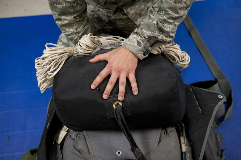 U.S. Air Force Senior Airman Erik Merrill, 31st Rescue Squadron aircrew flight equipment journeyman, packs a parachute June 20, 2016, at Kadena Air Base, Japan. A fully loaded parachute pack weighs approximately 80 pounds and contains both a main chute and reserve chute, adding an additional layer of safety for aircrews who jump out of aircraft. (U.S. Air Force photo by Senior Airman Peter Reft)