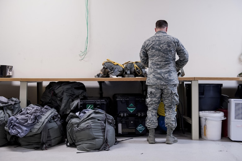 U.S. Air Force Senior Airman Erik Merrill, 31st Rescue Squadron aircrew flight equipment journeyman, inspects equipment June 20, 2016, at Kadena Air Base, Japan. Merrill assembles parachutes for pararescuemen and maintains a variety of aircrew equipment such as oxygen bottles, masks, life preservers, altimeters and night vision goggles. (U.S. Air Force photo by Senior Airman Peter Reft)