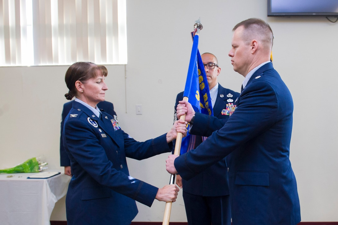 Col. Patricia Sergey, 369th Recruiting Group commander, presents Lt. Col. Joseph Roth, 333rd Recruiting Squadron commander, with the guidon during a change of command ceremony June 21, 2016, at Patrick Air Force Base, Fla. Changes of command are a military tradition representing the transfer of responsibilities from the presiding official to the upcoming official. (U.S. Air Force photo/James S. Rainier/Released)