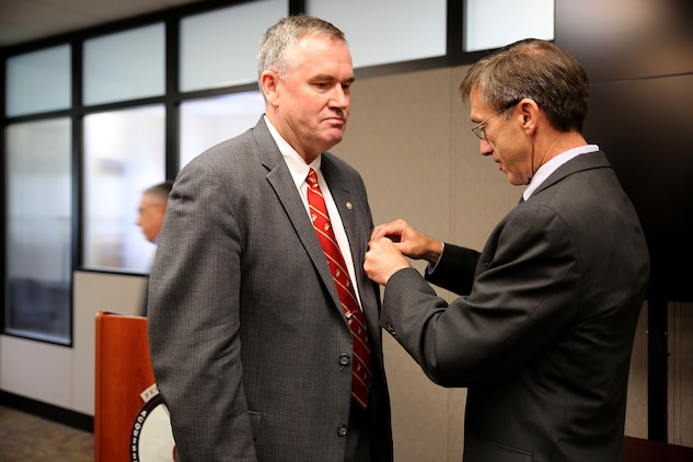 """The Honorable Sean Stackley (right), assistant secretary of the Navy for Research, Development and Acquisition, pins a Navy Distinguished Civilian Service medal on William """"Bill"""" Taylor during a Change of Leadership ceremony June 21 aboard Marine Corps Base Quantico, Virginia. Taylor, Program Executive Officer Land Systems and a member of the Senior Executive Service, has served as the Marine Corps' only PEO since 2007. Stackley lauded Taylor for taking several """"broken"""" programs and turning them into """"model"""" programs. """"The PEO's programs are strong, and the PEO is strong,"""" Stackley said. """"We wouldn't have that without this superior individual who wasn't just there at the beginning, but stayed for a decade."""""""