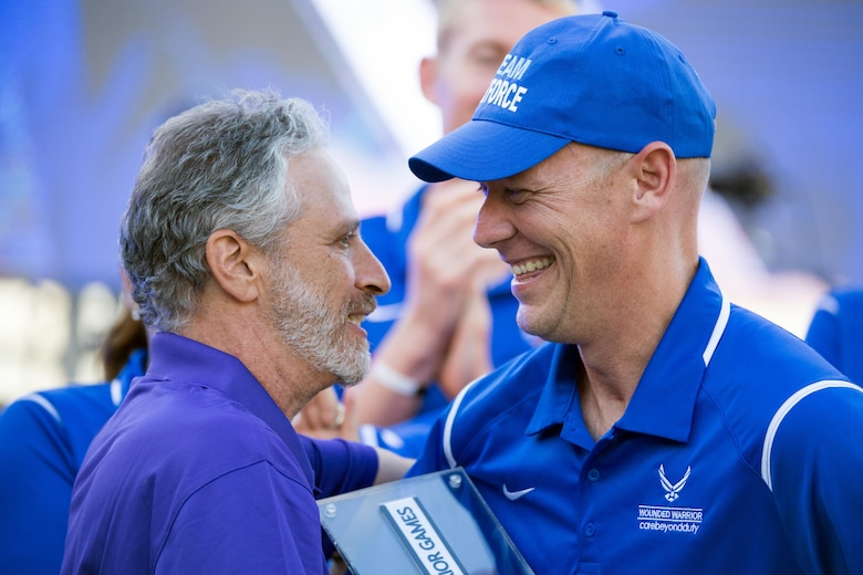 Comedian Jon Stewart, left, presents retired Air Force Capt. Chris Cochrane the Heart of Team Award for the Air Force team during the closing ceremony for the 2016 Department of Defense Warrior Games at the U.S. Military Academy in West Point, N.Y., June 21, 2016. DoD photo by EJ Hersom