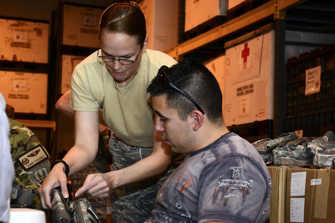 U.S. Air Force Tech. Sgt Jennifer Lotan, left, 379th Expeditionary Medical Support Squadron noncommissioned officer in charge of war rescue material, assists Staff Sgt. Michael Sanchez, 379th Operation Silent Sentry space systems operator, put together a joint first aid kit (JFAK) at Al Udeid Air Base, Qatar, June 15, 2016. Sanchez was one of more than 60 volunteers who assisted in the inspection and construction of more than 1,000 JFAKs.
