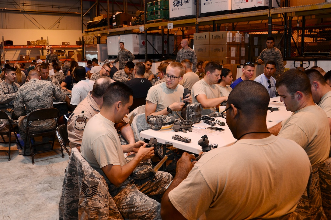 Volunteers inspect and assemble joint first aid kits (JFAK) at Al Udeid Air Base, Qatar, June 15, 2016. More than 60 volunteers, to include service members and Command Sponsorship Program spouses, participated in the JFAK building event. (U.S. Air Force photo by Senior Airman Kimberly Nagle)